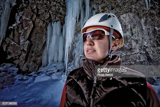 a young woman ice climber looking up at frozen waterfall - robb reece stock pictures, royalty-free photos & images