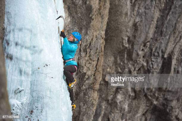 Young woman ice climbing on frozen waterfall