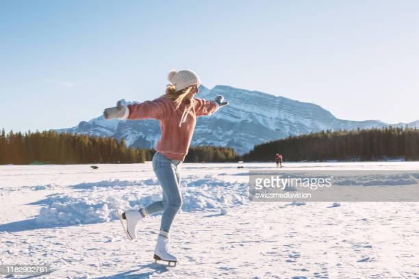 patinaje sobre hielo de mujer joven en el lago congelado al atardecer divirtiéndose y disfrutando de las vacaciones de invierno - patinar fotografías e imágenes de stock