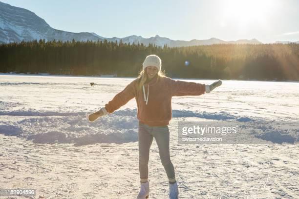 junge frau eislaufen auf gefrorenen see bei sonnenuntergang spaß haben und genießen winterurlaub - kieferngewächse stock-fotos und bilder