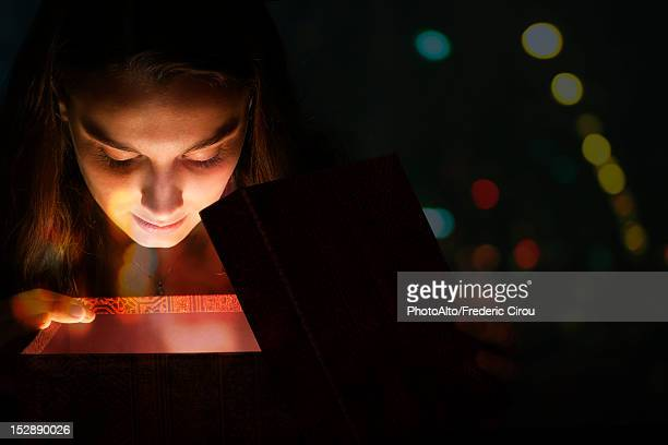 Young woman illuminated by light from within gift box