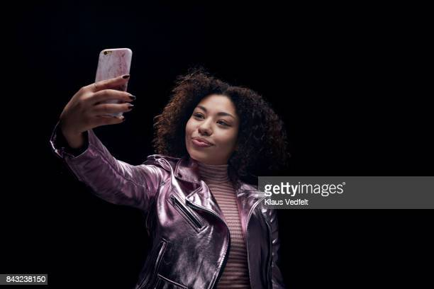 Young woman in 80' style purple jacket, making selfie with smartphone