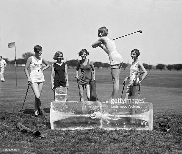 A young woman in a bathing suit tees off from a cake of ice on a hot day in Washington while four others await their turn Washington DC July 9 1926