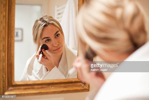 young woman in a bathrobe doing her makeup - blusher stock pictures, royalty-free photos & images