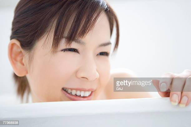 Young woman in a bathtub, smiling, close up, front view