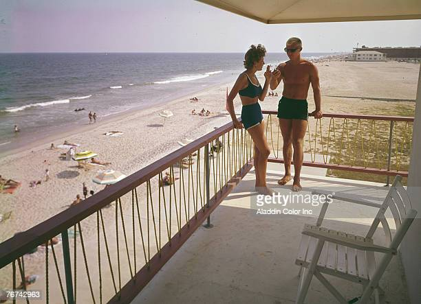 A young woman in a bikini accepts a light for her cigarette from a young man in suglasses and swimming trucks as they lean on the railing of a...