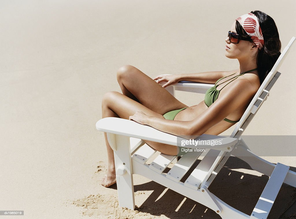 Young Woman in a Bikini Sitting on a Sun Lounger on a Beach : Stock Photo