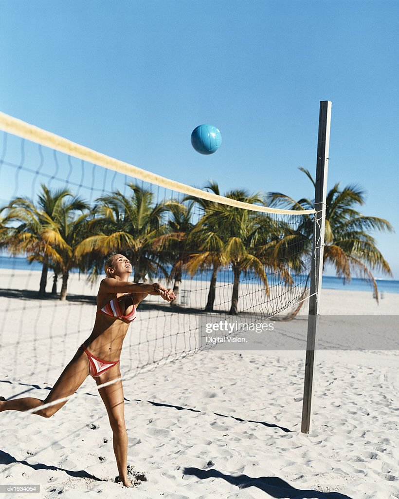 Young Woman in a Bikini Throws a Volleyball Over a Net on the Beach : Stock Photo