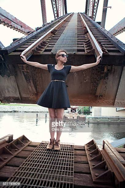 A young woman in a black dress stands in front of a railroad bridge.