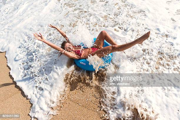 young woman in a blue rubber ring enjoying the beach - red tube stock pictures, royalty-free photos & images