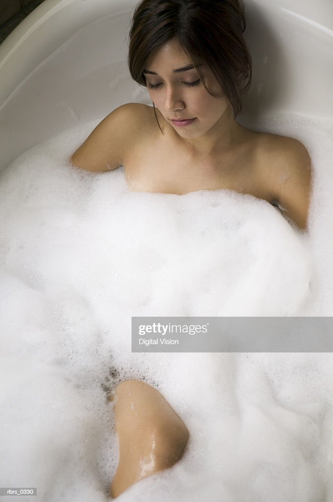 Young woman in a bubble bath with her eyes closed : Foto de stock