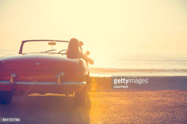 Young woman in a car at the beach.