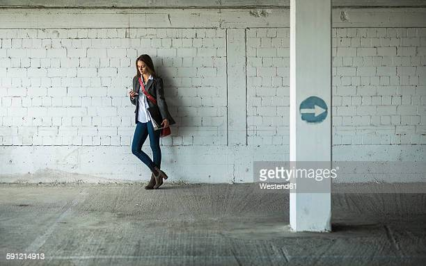 Young woman in a car park holding folder and looking at cell phone