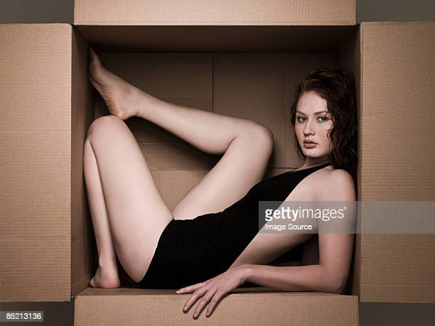 Young woman in a cardboard box