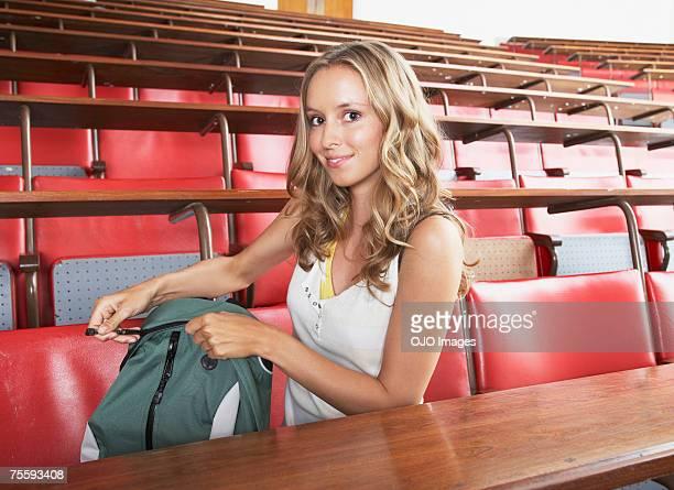 Junge Frau in einem Klassenzimmer leichtfüßig Ihr Rucksack