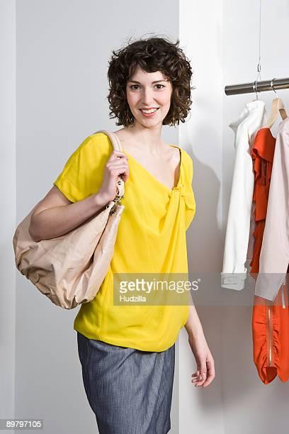 a young woman in a clothing store - sac à main blanc photos et images de collection