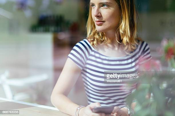 Young woman in a coffee shop looking through window