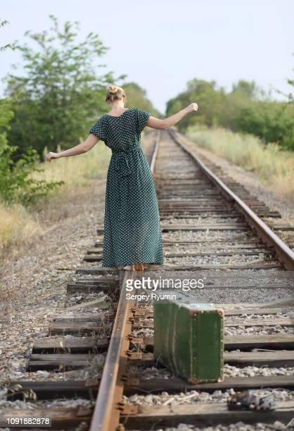 young woman in a dress balancing on a rail near her vintage suitcase. - grünes kleid stock-fotos und bilder