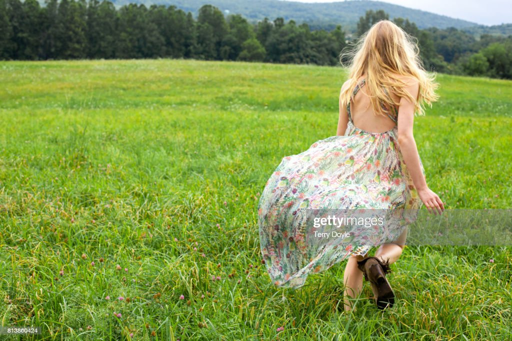 young woman in a floral dress running in a meadow : Stock Photo
