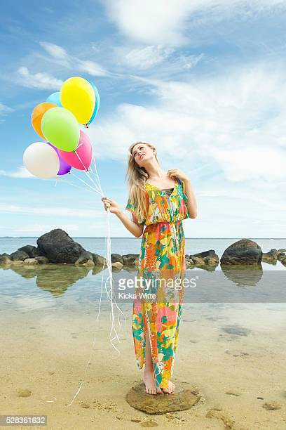 a young woman in a floral dress standing on the beach holding a bundle of colourful balloons; kauai, hawaii, united states of america - floral pattern dress stock pictures, royalty-free photos & images