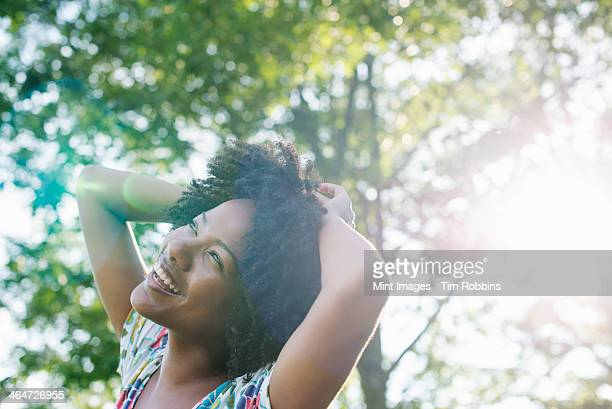 a young woman in a flowered summer dress with her hands behind her head, smiling and looking up. - one mid adult woman only stock pictures, royalty-free photos & images