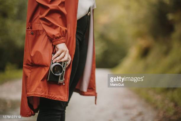 young woman in a forest using a vintage camera - vintage raincoat stock pictures, royalty-free photos & images