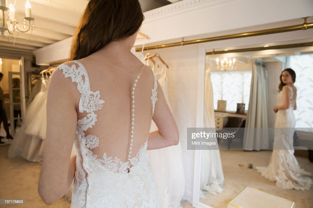 9dd75b44d92 A Young Woman In A Full Length White Wedding Dress Looking At Her ...