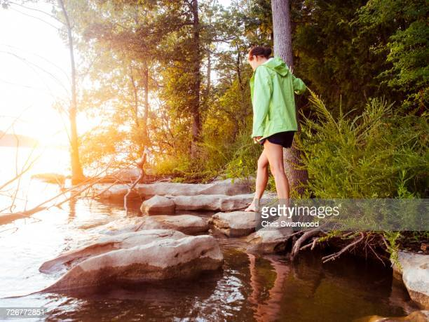 A Young Woman In A Green Jacket Walks Across Rocks On A Lake At Sunset