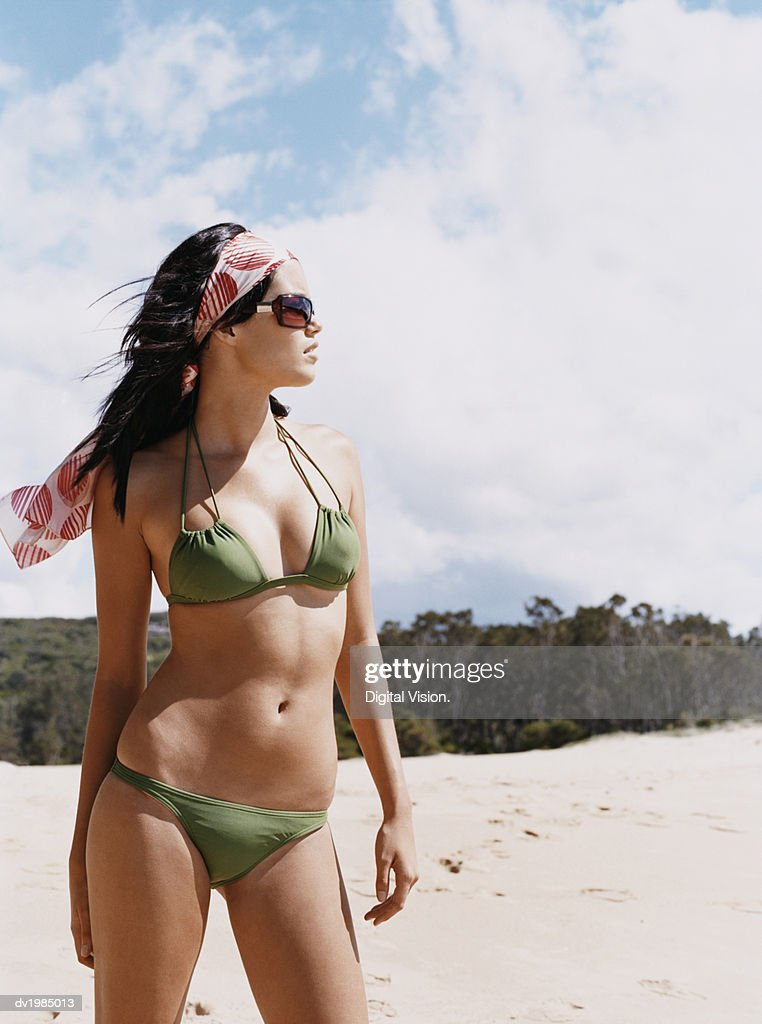 Young Woman in a Halterneck Bikini Standing on a Beach : Stock Photo