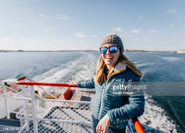 a young woman in a hat smiles while riding a ferry in portland maine - portland maine stock pictures, royalty-free photos & images