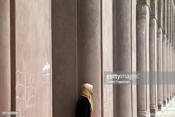 A young woman in a headscarf in the courtyard of the Ibn Tulun Mosque Cairo Egypt