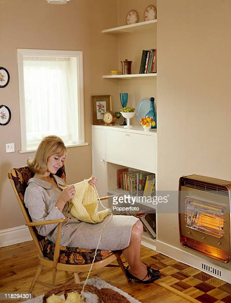 A young woman in a light grey woold dress knitting a yellow jumper beside a fire in her living room circa 1960