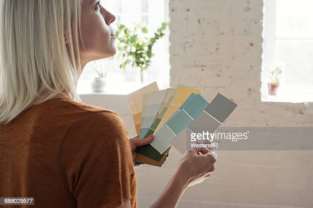 young woman in a loft thinking about color samples - escolher - fotografias e filmes do acervo