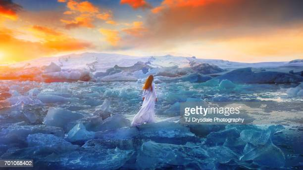 Young woman in a long dress standing at iceland's glacial lagoon, Jökulsárlón, looking away