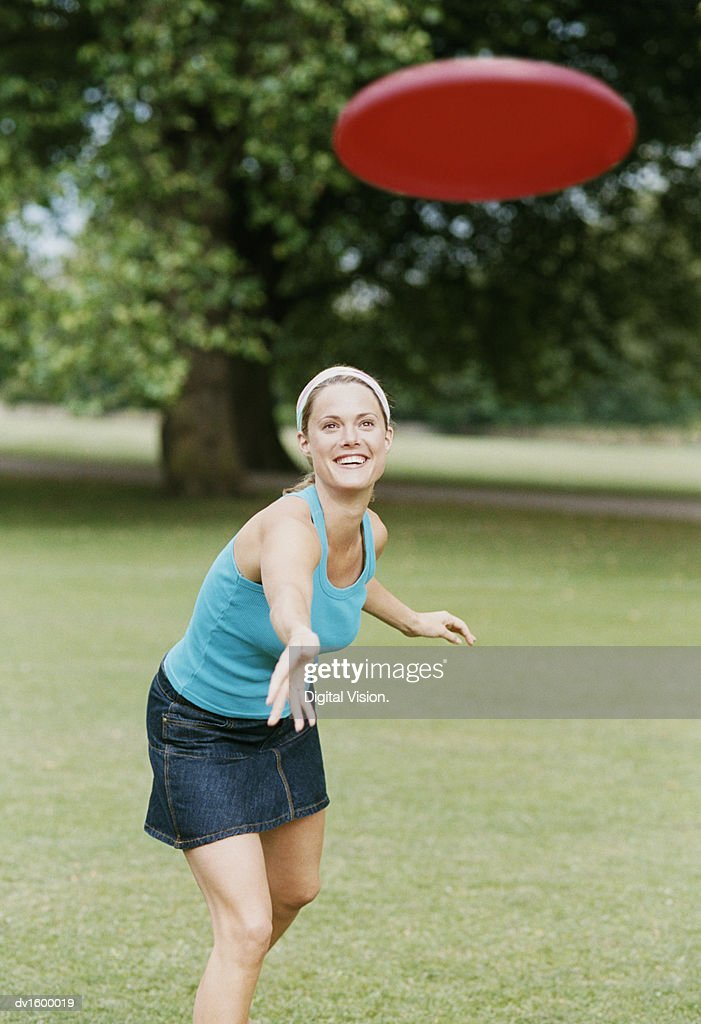 Young Woman in a Park Throwing a Frisbee : Stock Photo