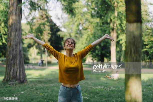 young woman in a park with outstretched arms - zufriedenheit stock-fotos und bilder