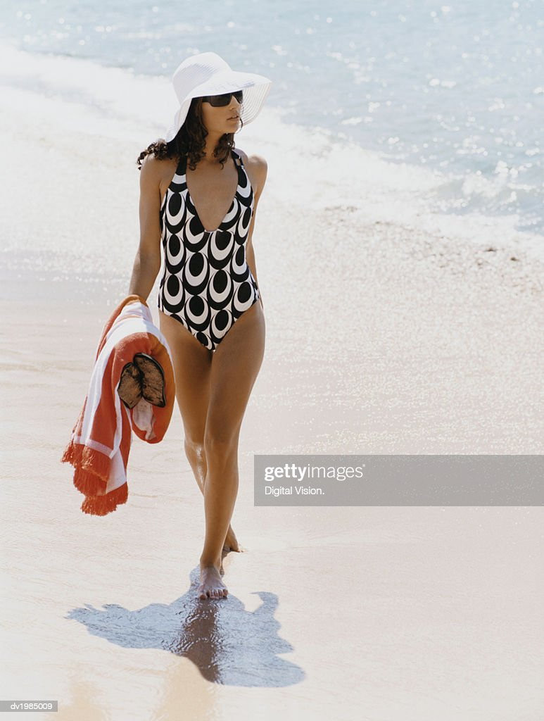 Young Woman in a Patterned Swimsuit and Sunhat Walks Along the Beach Carrying a Towel : Stock Photo