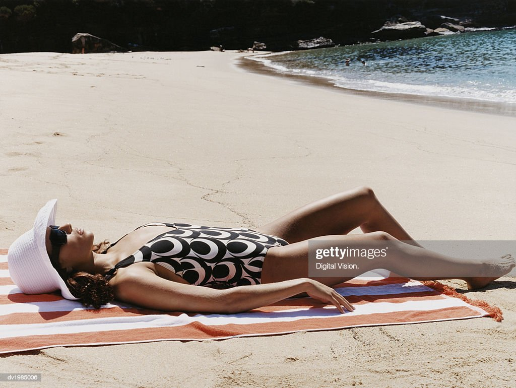 Young Woman in a Patterned Swimsuit Sunbathes on the Beach : Stock Photo