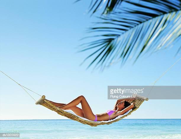 Young Woman in a Pink Bikini Lying in a Hammock Beside the Sea, Sunbathing