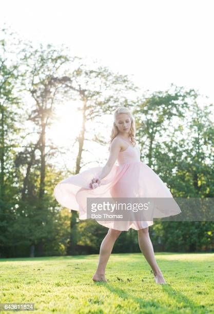 young woman in a pink dress dancing in a garden - backlit - ダンス ドレス ストックフォトと画像