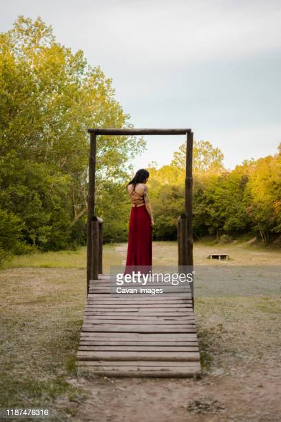 young woman in a red dress on a wooden platform. fantasy - red dress stock pictures, royalty-free photos & images