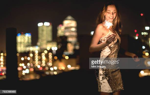 a young woman in a sequined dress dancing on a rooftop at night holding a party sparkler. - cocktail dress stock pictures, royalty-free photos & images