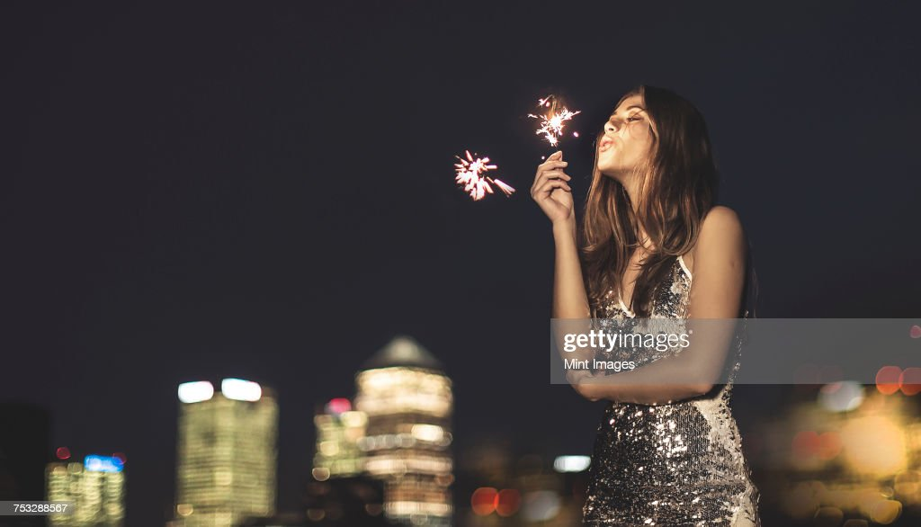 A young woman in a sequined dress dancing on a rooftop at night holding a party sparkler. : Stockfoto