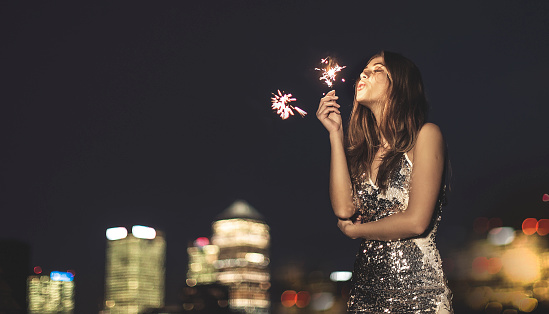 A young woman in a sequined dress dancing on a rooftop at night holding a party sparkler. - gettyimageskorea