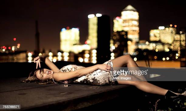a young woman in a sequined party dress lying back on a rooftop laughing and waving. - seduction stock pictures, royalty-free photos & images