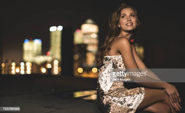 A young woman in a sequined party dress sitting on a rooftop at night.