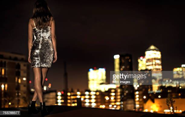 a young woman in a sequined party dress standing on a rooftop at night looking at the city lights. - イブニングウェア ストックフォトと画像