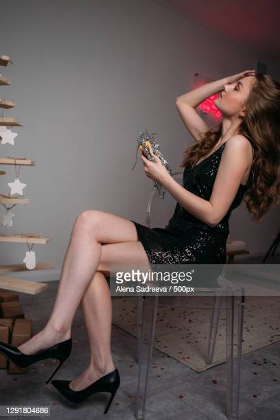 young woman in a shiny black dress holding a sandwich filled with christmas tinsel,russia - silver shoe stock pictures, royalty-free photos & images
