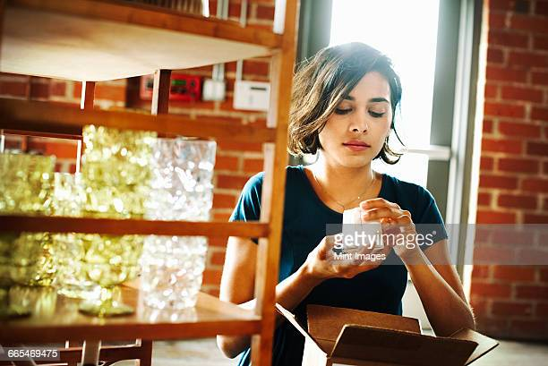 Young woman in a shop, holding a small ceramic object.