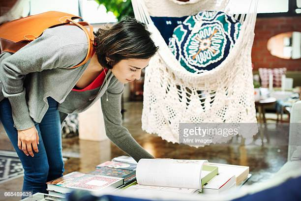 Young woman in a shop, looking at books.